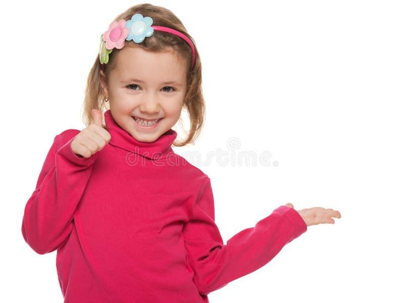 Bambina allegra nel rosso con il suo pollice su immagine stock