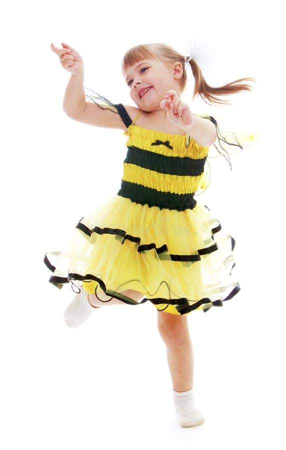 Bambina allegra in un vestito giallo che salta e immagini stock