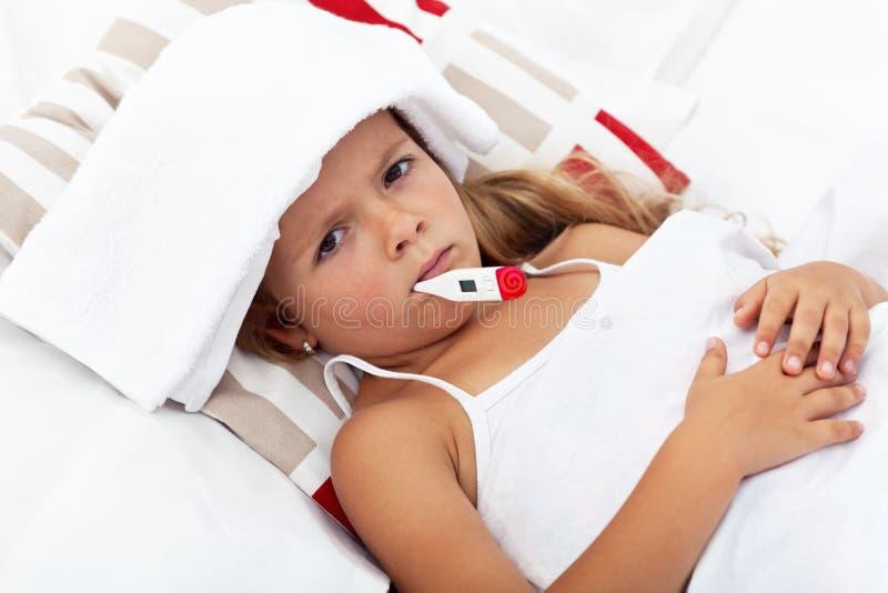Bambina ammalata con il termometro e l'impacco freddo immagini stock libere da diritti