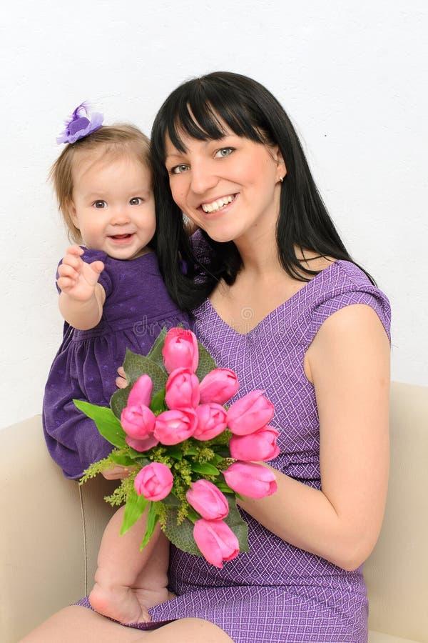 Bambina in armi di sua madre. Tenga i fiori fotografia stock libera da diritti