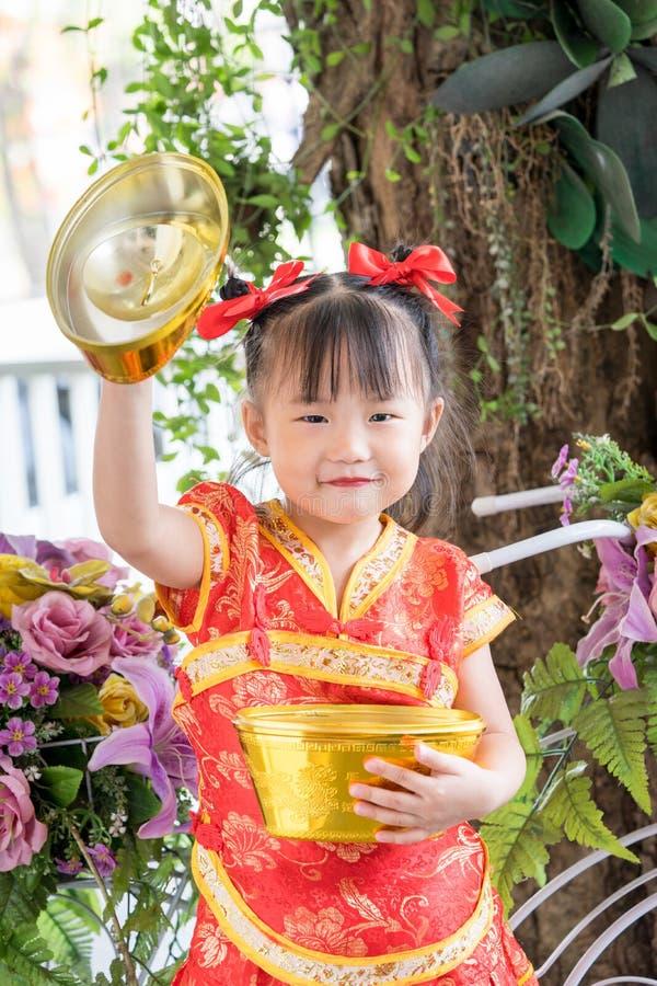 Bambina asiatica che indossa il vestito rosso del cinese tradizionale immagini stock