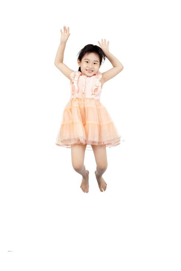 Bambina asiatica che salta nell'aria fotografie stock libere da diritti