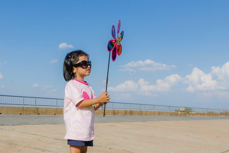 Bambina asiatica con il giocattolo del generatore eolico in mani fotografie stock