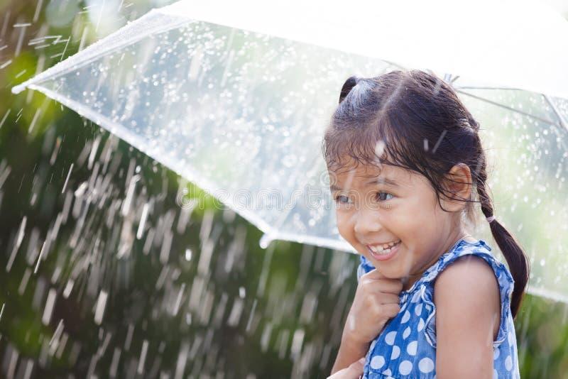 Bambina asiatica con l'ombrello in pioggia fotografia stock
