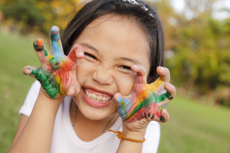 Ragazza con le mani dipinte in pitture variopinte immagine stock libera da diritti