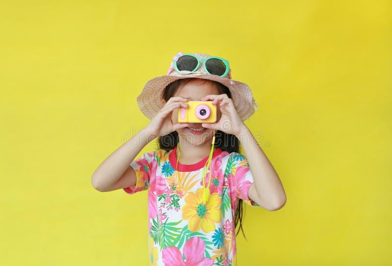 Bambina asiatica con un abito estivo a modello floreale e un cappello con occhiali da sole che scattano foto con una fotocamera g fotografia stock libera da diritti