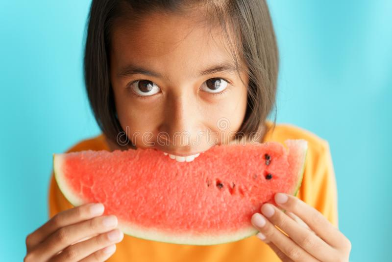 Bambina asiatica dell'immagine del ritratto che mangia anguria su fondo blu Un bambino della ragazza così felice dopo mangia l'an fotografie stock libere da diritti