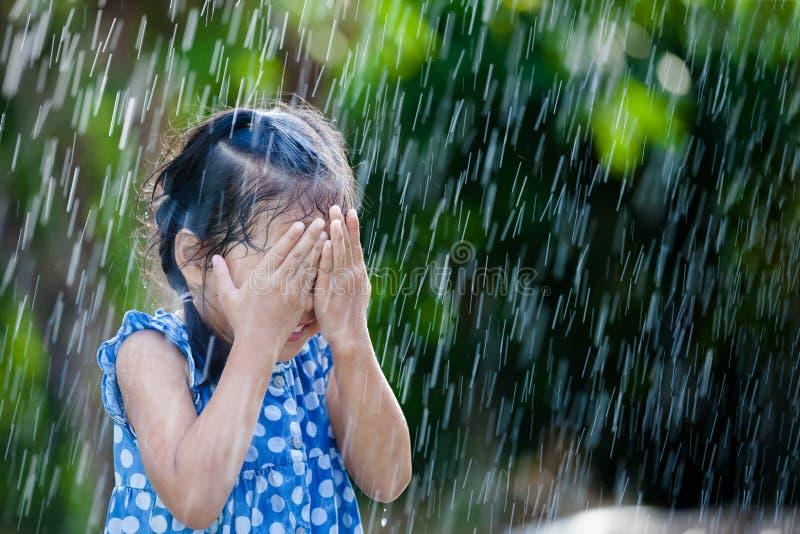 Bambina asiatica divertendosi da giocare con la pioggia fotografia stock