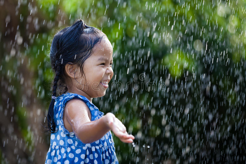 Bambina asiatica divertendosi da giocare con la pioggia fotografie stock libere da diritti