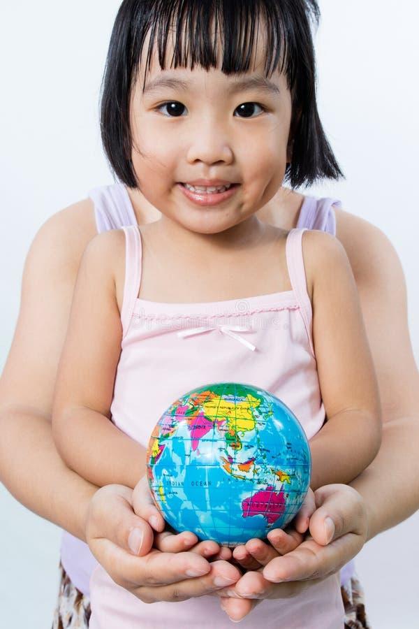 Bambina asiatica ed adulto che tengono un globo del mondo in mani immagini stock libere da diritti