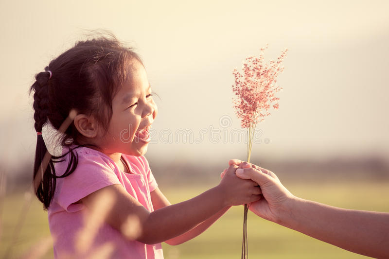 Bambina asiatica felice che dà il fiore dell'erba a sua madre immagine stock