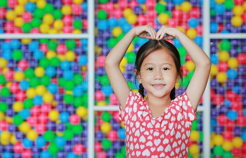 Bambina asiatica felice che fa il segno del cuore sulla testa contro il campo da giuoco variopinto della palla Esprime le emozion immagini stock