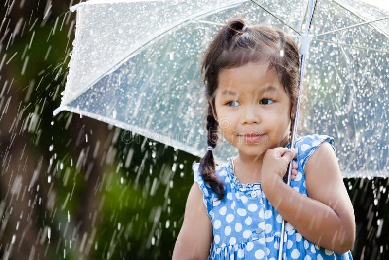 bambina asiatica sveglia con l'ombrello in pioggia immagine stock
