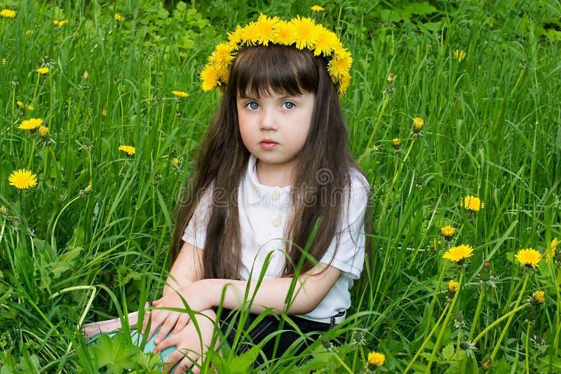 Bambina attenta in una corona dai denti di leone immagine stock libera da diritti