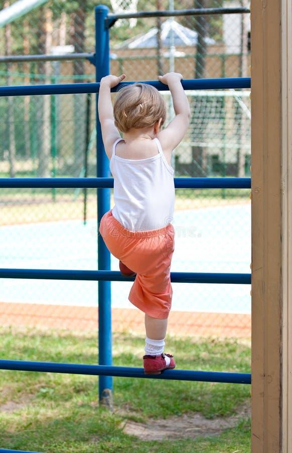Bambina attiva che si arrampica su una scaletta immagine stock