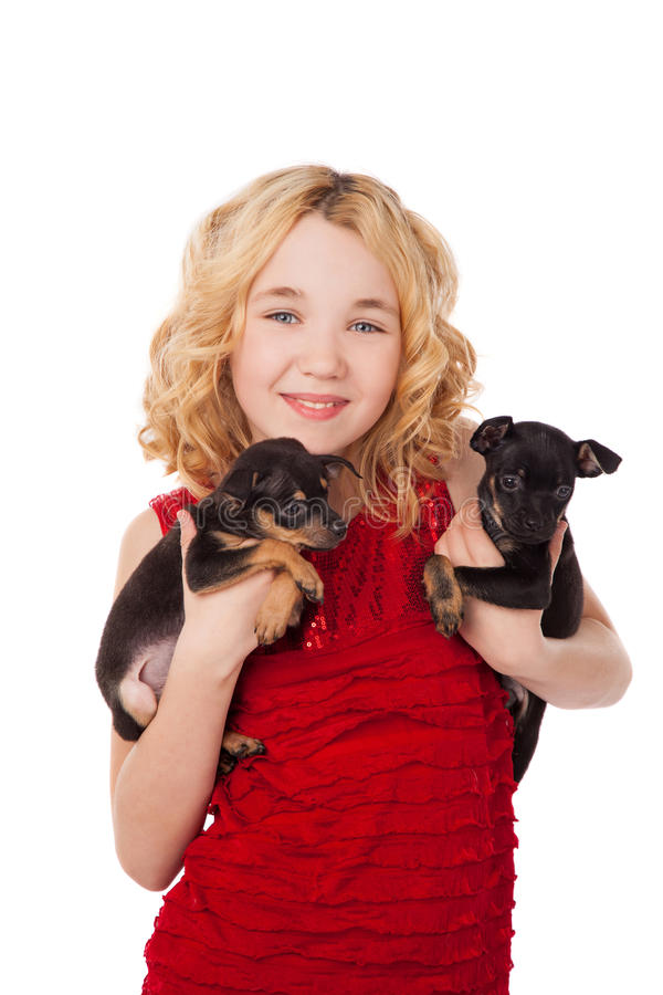 Bambina bionda che tiene due cuccioli che portano vestito rosso fotografia stock libera da diritti