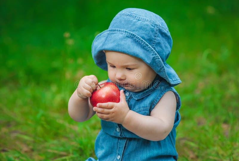 Bambina in blue jeans ed in un cappello sulla sua testa in un vestito blu che si siede un giorno soleggiato nel parco sull'erba fotografia stock