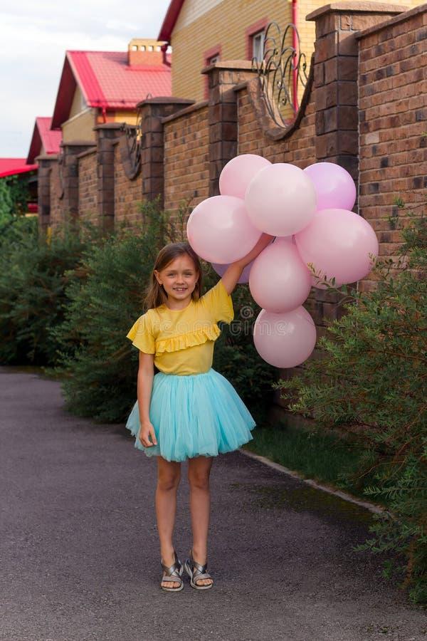 bambina in camicia gialla e gonna blu che sorride e che tiene molti palloni, infanzia felice e concetto di estate immagini stock
