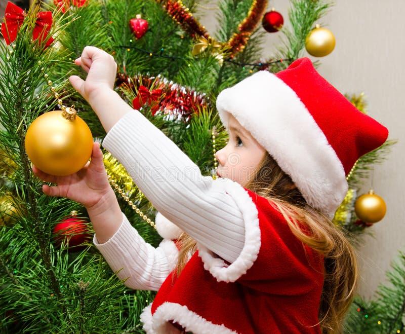 Bambina in cappello di Santa che decora l'albero di Natale fotografia stock libera da diritti