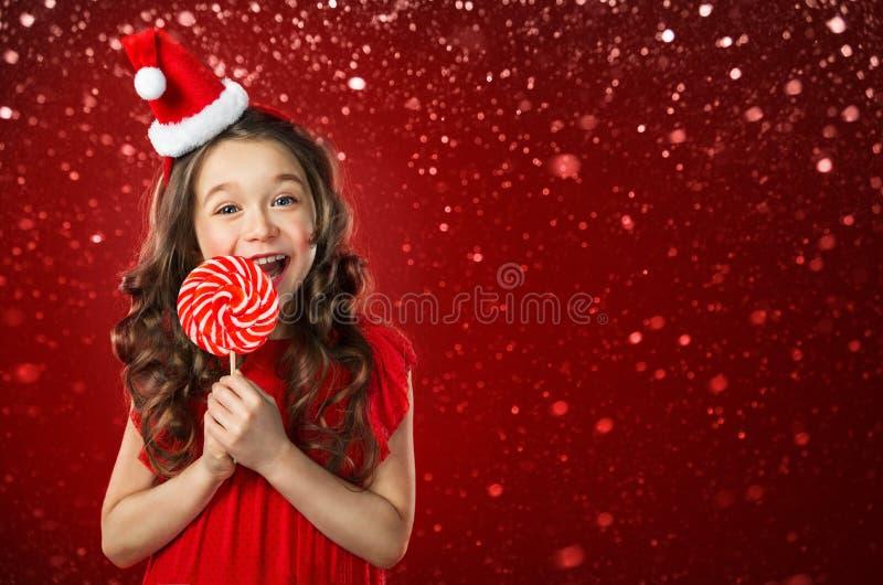 Bambina in cappello di Santa con la caramella su fondo rosso Tempo di natale immagine stock libera da diritti