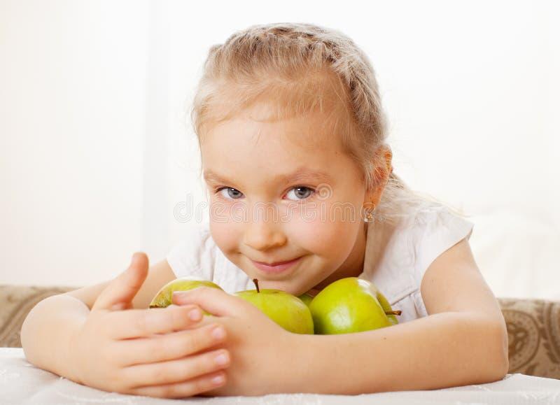 Bambina a casa con le mele immagine stock
