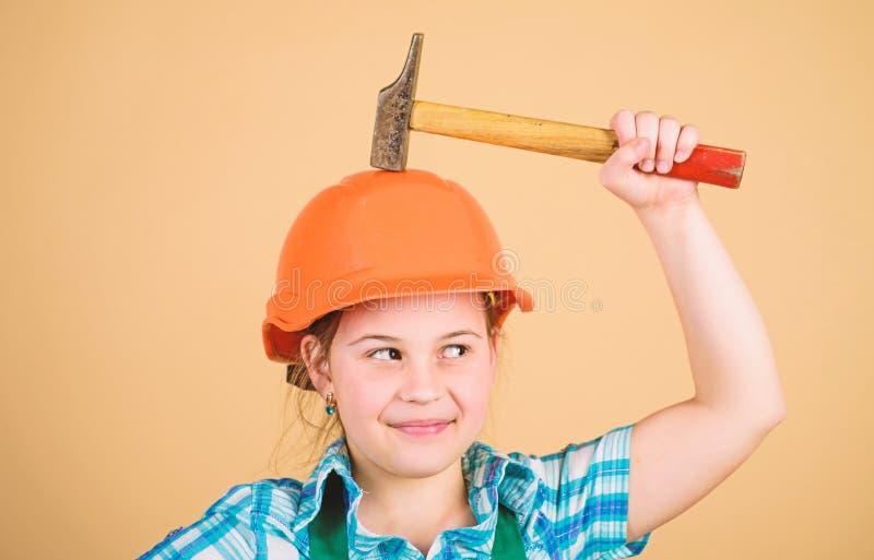 Bambina in casco con il martello Lavoratore del bambino in casco piccola ragazza che ripara nell'officina Esperto in sicurezza fu fotografia stock libera da diritti