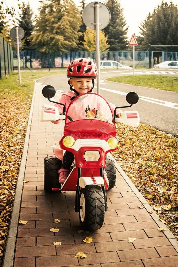 Bambina in casco sulla motocicletta sul campo da giuoco immagine stock