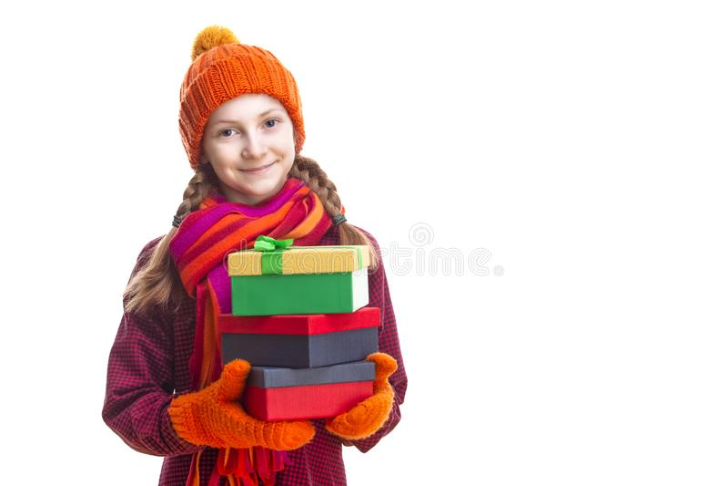 Bambina caucasica felice sorridente in Beanie, sciarpa e guanti arancio con il mucchio di Giftboxes variopinto Isolato contro pur fotografia stock