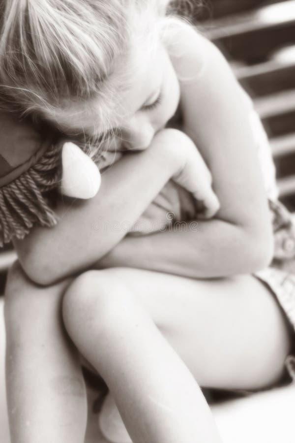 Bambina che abbraccia il fuoco molle del giocattolo fotografia stock libera da diritti