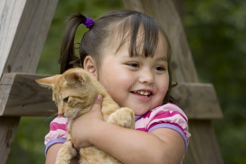 Bambina che abbraccia il suo gattino immagine stock
