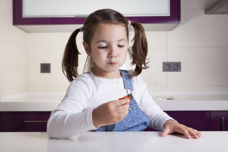 Bambina che assaggia un pomodoro ciliegia variopinto crudo fotografia stock