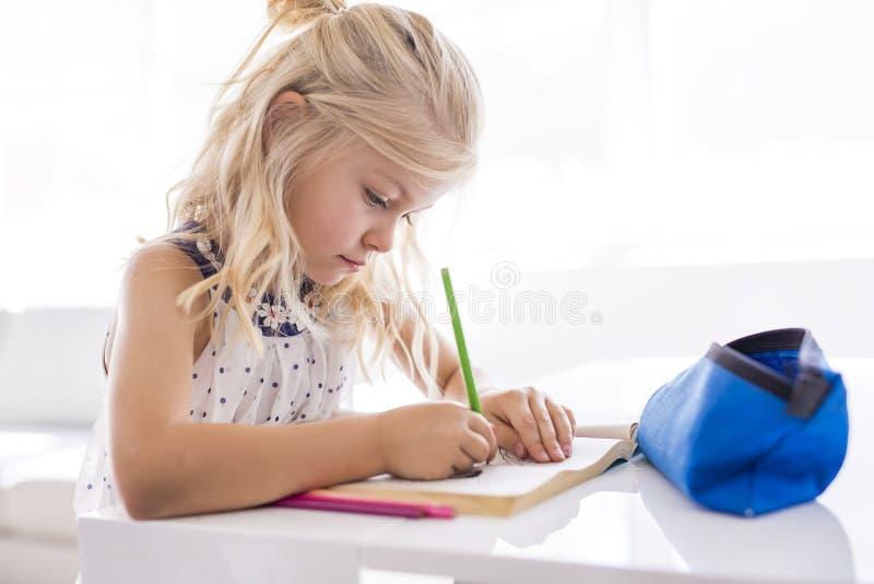Bambina che assorbe il tavolo da cucina immagine stock libera da diritti