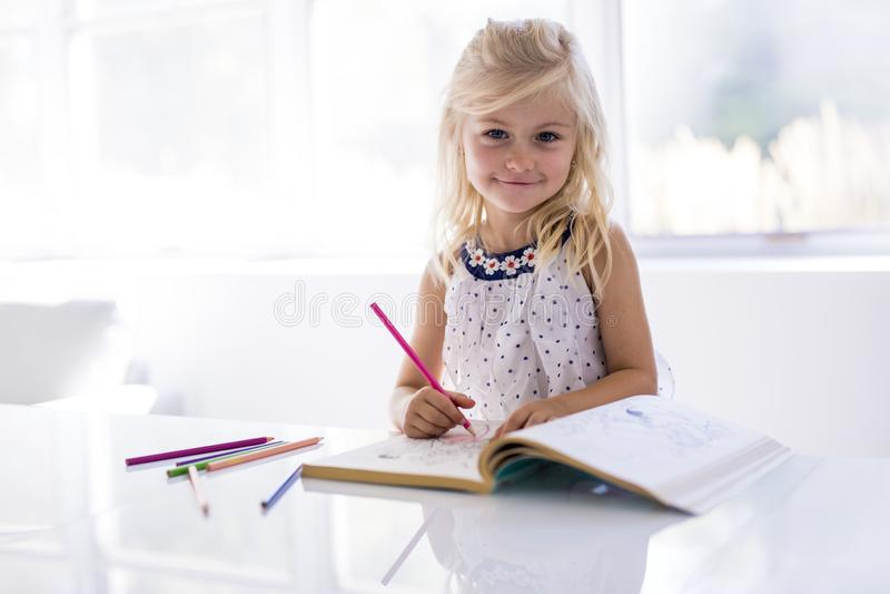 Bambina che assorbe il tavolo da cucina fotografie stock