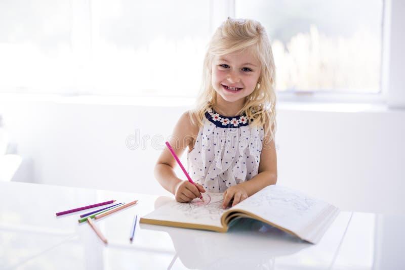 Bambina che assorbe il tavolo da cucina immagini stock libere da diritti