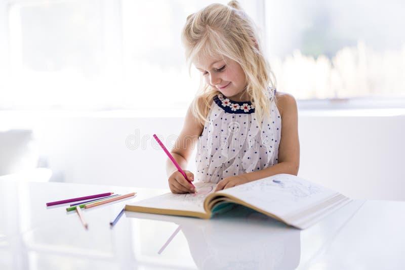 Bambina che assorbe il tavolo da cucina fotografia stock