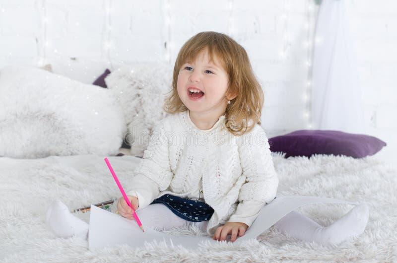 Bambina che assorbe letto fotografia stock