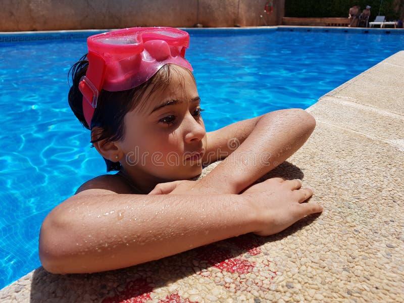 Bambina che bagna in uno stagno con gli occhiali di protezione d'immersione fotografia stock
