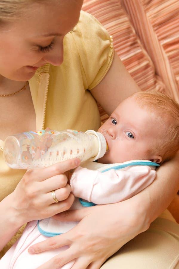 Bambina che beve dalla bottiglia di plastica fotografia stock
