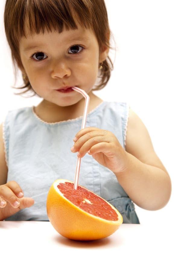Bambina che beve una spremuta di pompelmo fotografia stock