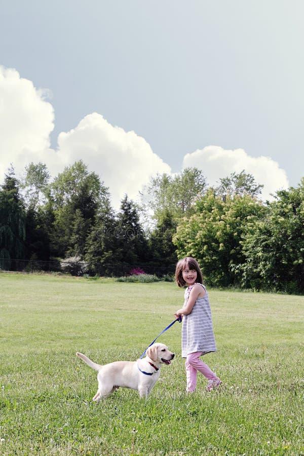 Bambina che cammina il suo cucciolo fotografia stock