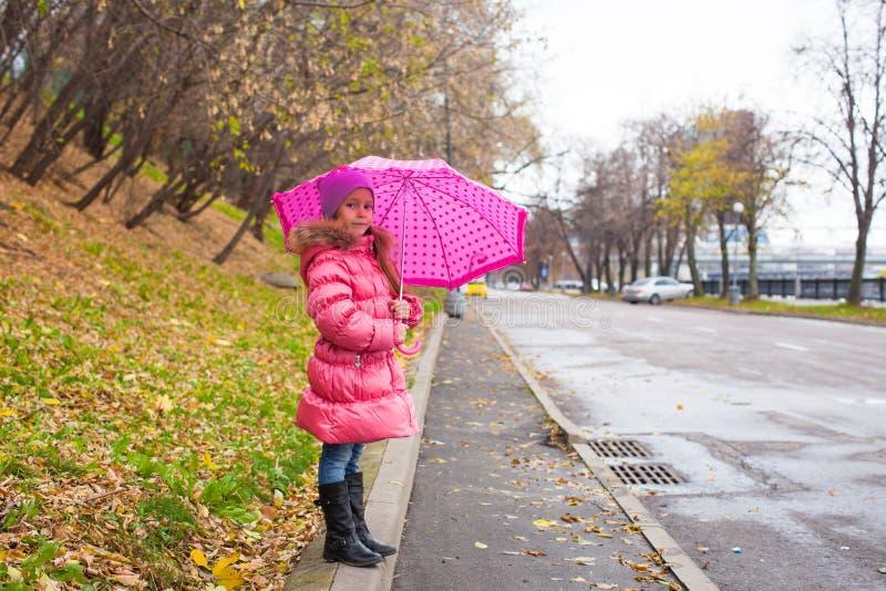 Bambina che cammina sotto un ombrello in fotografia stock