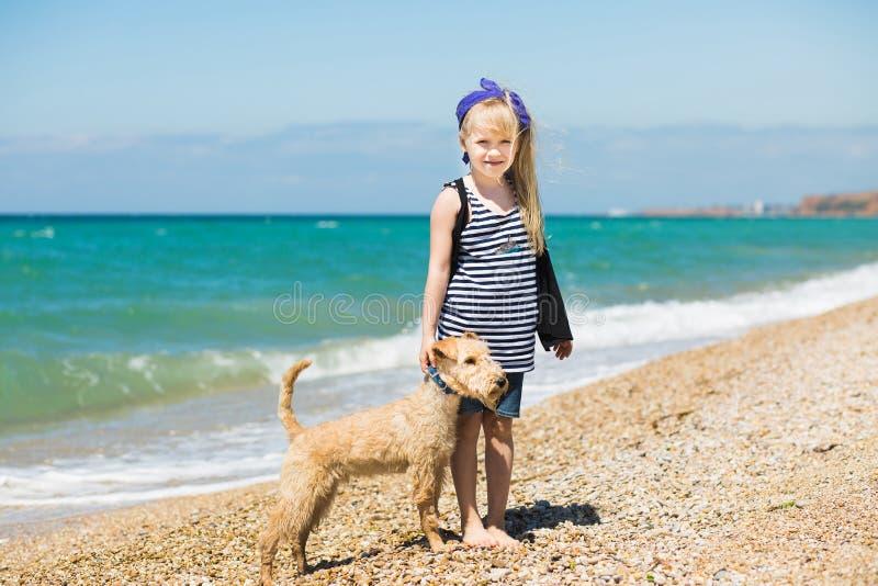 Bambina che cammina sulla spiaggia con un terrier del cucciolo immagini stock libere da diritti