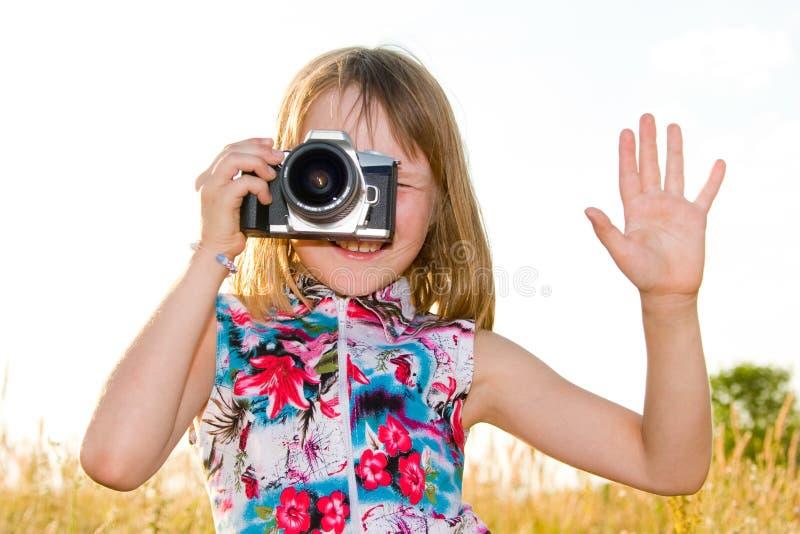 Bambina che cattura maschera con la macchina fotografica di SLR fotografia stock libera da diritti