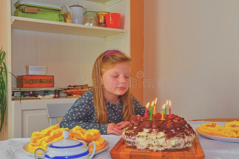 Bambina che considera la sua torta di compleanno Piccola ragazza che celebra i suo sei compleanni Torta di compleanno e bambina fotografie stock