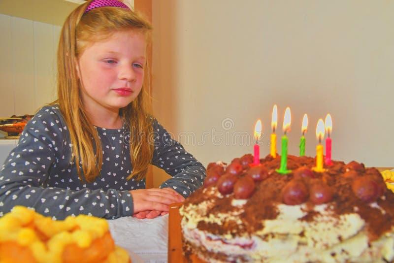 Bambina che considera la sua torta di compleanno Piccola ragazza che celebra i suo sei compleanni Torta di compleanno e bambina immagini stock