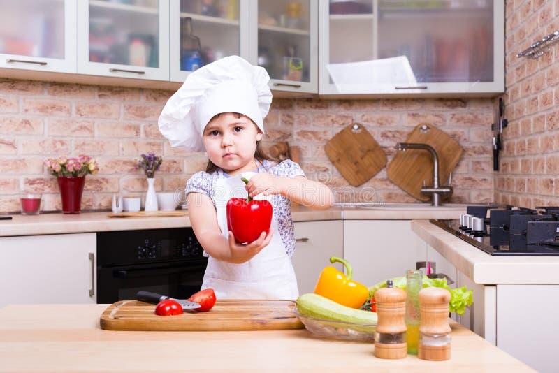 Bambina che cucina gli ortaggi freschi sulla cucina domestica immagine stock