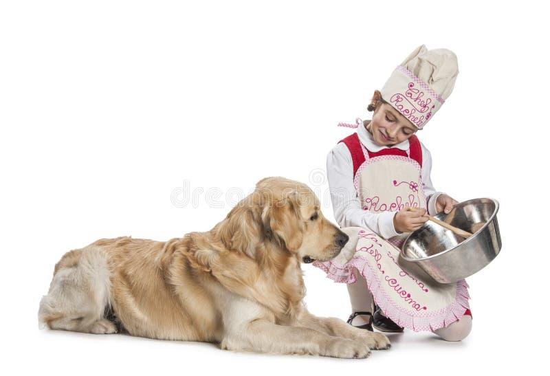 Bambina che cucina per il suo cane fotografia stock libera da diritti