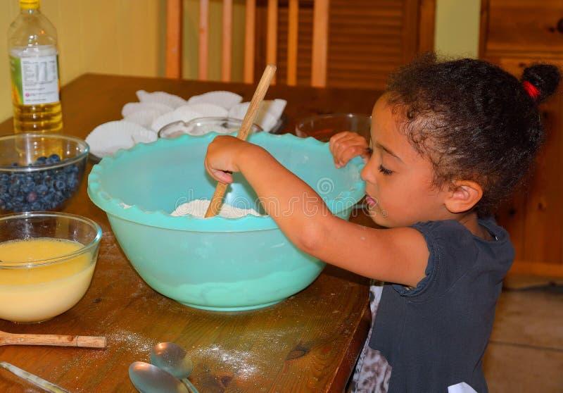 Bambina che cuoce felicemente fotografia stock