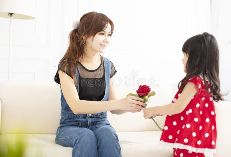 Bambina che dà un fiore a sua madre fotografia stock