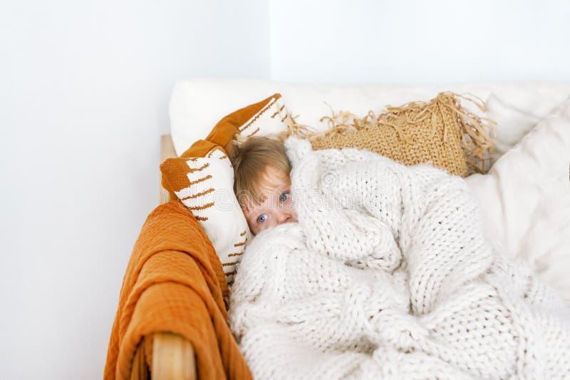Bambina che dà una occhiata fuori a generale sul letto Bambino sveglio che sorride e che si nasconde nell'ambito della copertura  fotografie stock libere da diritti